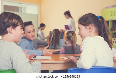 Happy pupils chattering sitting on back desks at lesson in elementary school