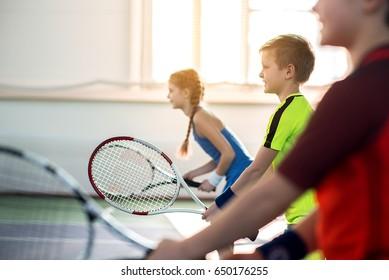 Happy pupils enjoying tennis game