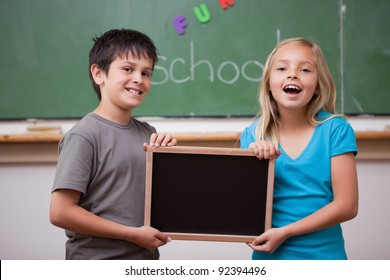 Happy pupils holding a school slate in a classroom