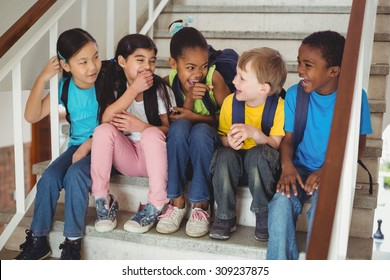 Happy pupils laughing and sitting on stairs in school