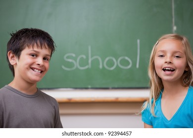 Happy pupils posing together in front of a chalkboard