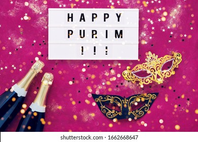 Happy Purim written in light box, two champagne bottles, carnival mask and golden confetti on purple background. Flat lay of Purim Carnival celebration concept. Top view, copy space for text.