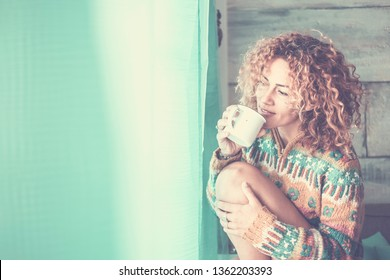 Happy quiet and peaceful young attractive woman enjoy the relax time at home drinking a cup of tea and looking outside the window - curly hair for caucasian people