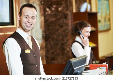 Happy receptionist worker standing at hotel counter