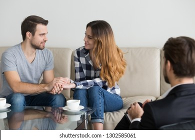 Happy reconciled young couple holding hands satisfied with family therapy session visiting psychologist counselor, loving spouses making peace forgive and find compromise, marriage counseling concept