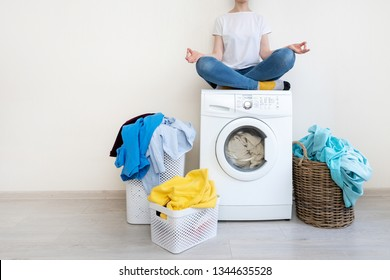 Happy and recreation lady in denim jeans wear sitting near laundry basket inside bright light flat interior with copy space for text on top of washing machine in meditation pose