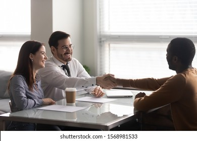 Happy recruiter handshake greeting with african American male work candidate at interview in office, smiling HR manager shake hand of man applicant closing deal thanking for successful talk