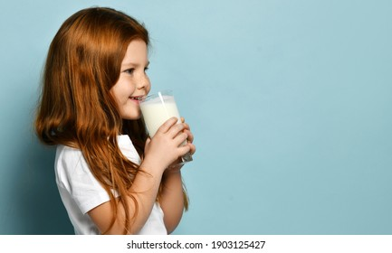 Happy red haired kid girl stands side to camera holding glass of milk drinking looking at copy space over light blue background. Health and diet concept. Healthy drink breakfast and clean food concept