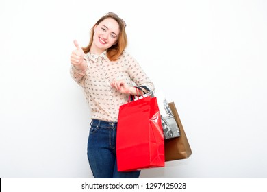 Happy red-haired beautiful woman on a light background with bags after shopping showing thumbs up. The modern concept of fashion, style, beauty.