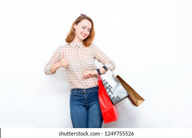 Happy red-haired woman in stylish casual clothes with bags after shopping and showing thumbs up. Modern concept of fashion, shopping, discounts, sales.