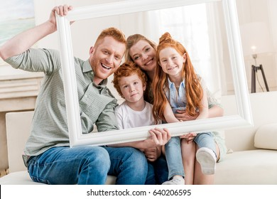 happy redhead family looking through white frame together, big family portrait concept