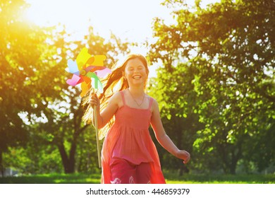 Happy redhead girl with pinwheel toy in park. Freedom, summer, childhood concept