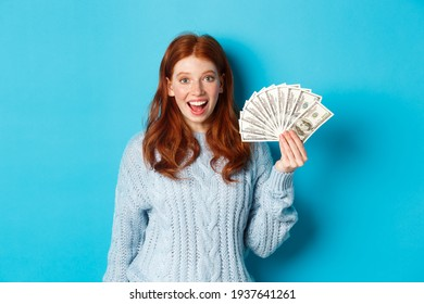 Happy redhead girl in sweater, staring excited at camera, showing money dollars, standing against blue background