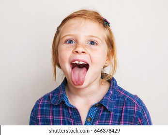 Happy redhead little girl in blue plaid shirt showing her tongue.