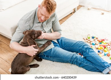 happy redhead man playing with labrador retriever puppy at home