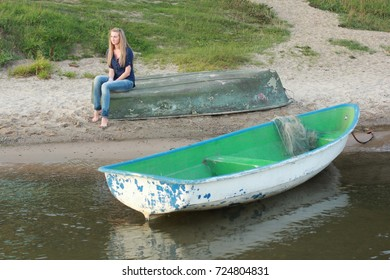 Happy redhead woman, relax on old boat at summer shore