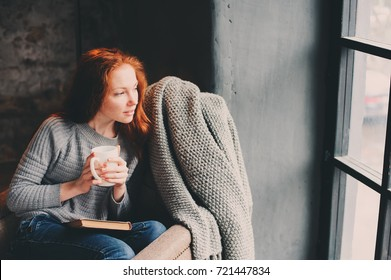 happy redhead woman relaxing at home in cozy winter or autumn weekend with book and cup of hot tea, sitting in soft chair with blanket