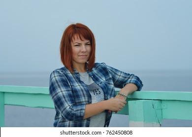 happy redhead woman standing near the sea