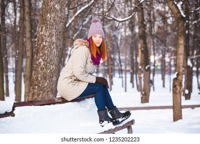 Happy redhead woman walking in winter park and enjoy the snow. Concept picture