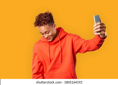 Happy redhead, young adult millennial wearing in casual hoodie clothes, standing against orange background with copy space. Man holding smartphone in hands and smiling nice