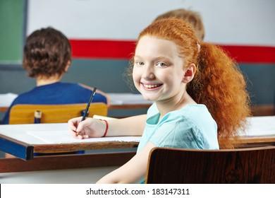 Happy redheaded girl smiling in elementary school class