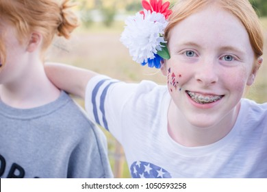 Happy redheaded teen enjoying the 4th of July festivities with friends and themed accessories and clothing.