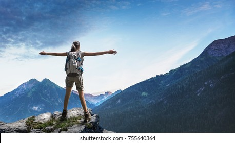 Happy rejoicing woman wearing backpack with arms outstretched on rocky cliff looking at wide mountains in the distance