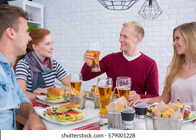 Happy and relax friends are sitting together during meal