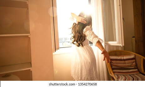 Happy and relax time in the morning of Woman standing near the window which  stretching near bed after waking up with sunrise at morning and lens flare, back view