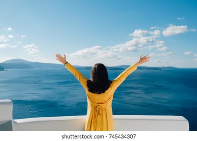 Happy relax woman arms raised up to blue sky feel freedom on vacation, Female in yellow dress outdoors celebrating or worship god in a beautiful sky, Santorini Greece