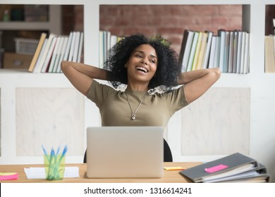 Happy relaxed african female worker student satisfied with finished work study at workplace, carefree black lady holding hands behind head taking break after job well done enjoy no stress free relief