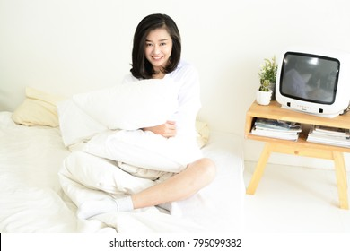 Happy relaxed Asain woman hugging pillow on bed