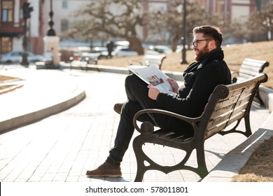 Happy relaxed bearded young man in glasses reading newspaper on the bench outdoors