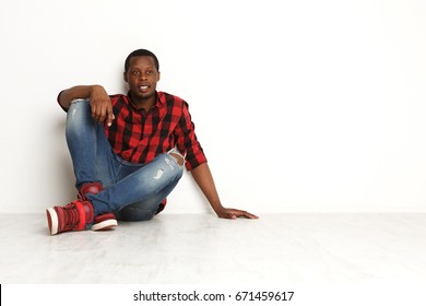 Happy relaxed black man sitting with crossed legs at white studio background, smiling man in checkered shirt