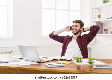 Happy relaxed businessman has a mobile talk at modern white office.
