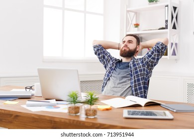 Happy relaxed businessman in office. Handsome man in casual, confident and successful employee at work with computer. Lifestyle portrait