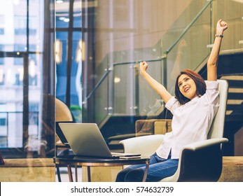 Happy relaxed casual woman sitting on the chair with a laptop in front of her stretching her arms above her head and looking out of the window with a smile.