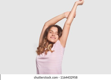 Happy relaxed Caucasian woman stretches after awakening, being in good mood as saw pleasant dreams, dressed in nightwear, ready to start new day, stands against white background. Rest concept