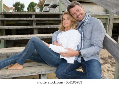 Happy relaxed couple dressed casual lying on the stairs.