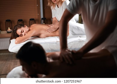 Happy relaxed couple getting body care treatment having peaceful calm expression while lying on massage beds in spa resort.