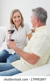 Happy relaxed couple with wine glasses sitting on sofa at home