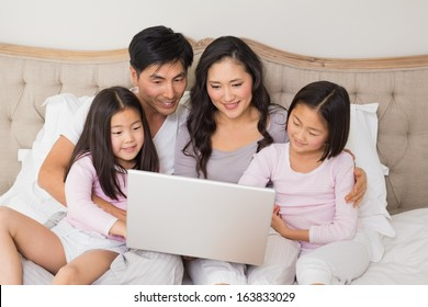 Happy relaxed family of four using laptop in bed at home