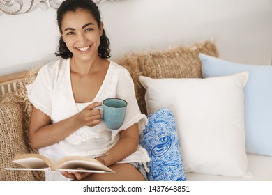 Happy relaxed good-looking tanned brunette woman enjoy weekend day-off stay home indoors sitting comfortable rattan couch living room look camera smiling broadly hold coffee mug reading book