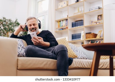 Happy relaxed man enjoying listening to music on stereo headphones using his mobile phone in a low angle view of him sitting on a sofa at home