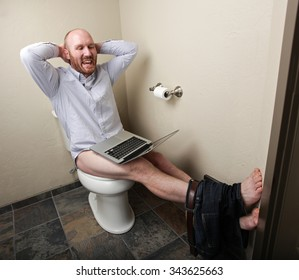 A happy relaxed man on his computer while on the toilet