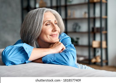 Happy relaxed mature old woman resting dreaming sitting on couch at home. Smiling mid aged woman relaxing. Peaceful serene grey-haired lady feeling peace of mind enjoying lounge on sofa and thinking. - Shutterstock ID 1818577409