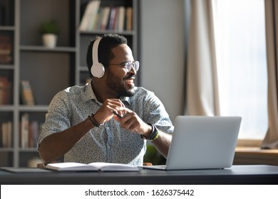 Happy relaxed millennial afro american business man wear wireless headphones look away rest at workplace finished work listening music podcast feel peace of mind concept sit at desk in sunny office