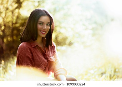 Happy relaxed teen girl with perfect white smile outdoor bokeh effect copy space