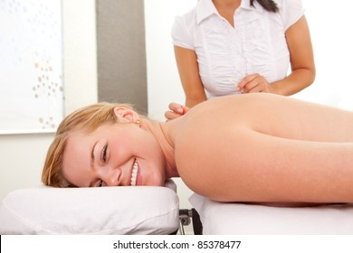 Happy relaxed woman acupuncture patient receiving a therapy treatment on the back