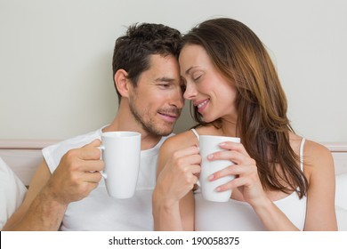 Happy relaxed young couple with coffee cups at home